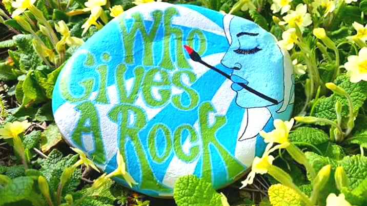 Blue and Green Who Gives A Rock Painted Stone Logo with picture of female artist holding paintbrush with rays of sunshine